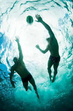 Water polo players chasing ball