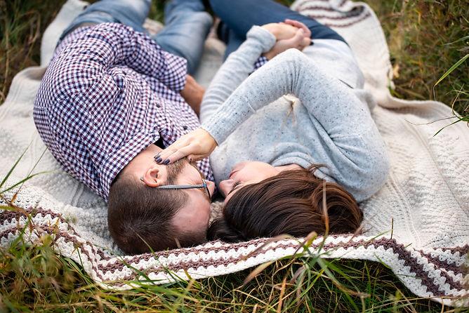Engagement photo of couple on blanket by Alberta Wedding Photographer