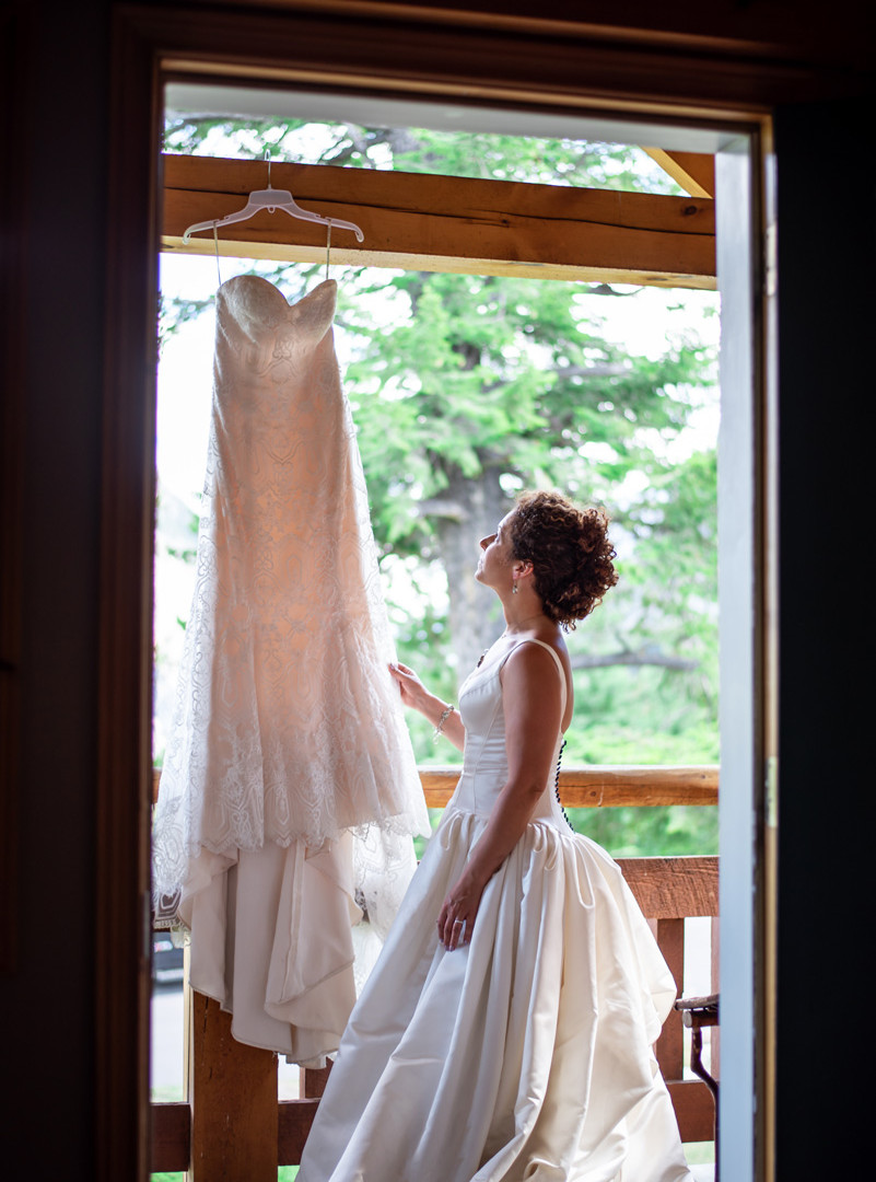 Image of bride looking at wedding dress at Tunnel Mountain Resort in Banff, AB
