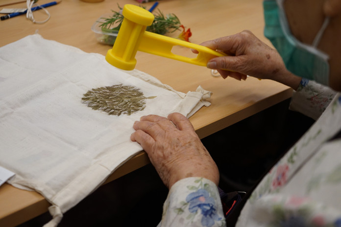 An old lady pressing a leaf on her fabric bag
