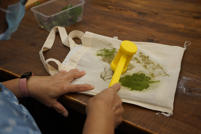 An old lady pressing leaves on a fabric bag