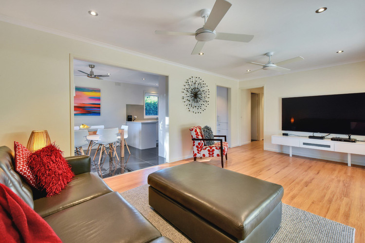 """Living area with 75"""" wall mounted television"""