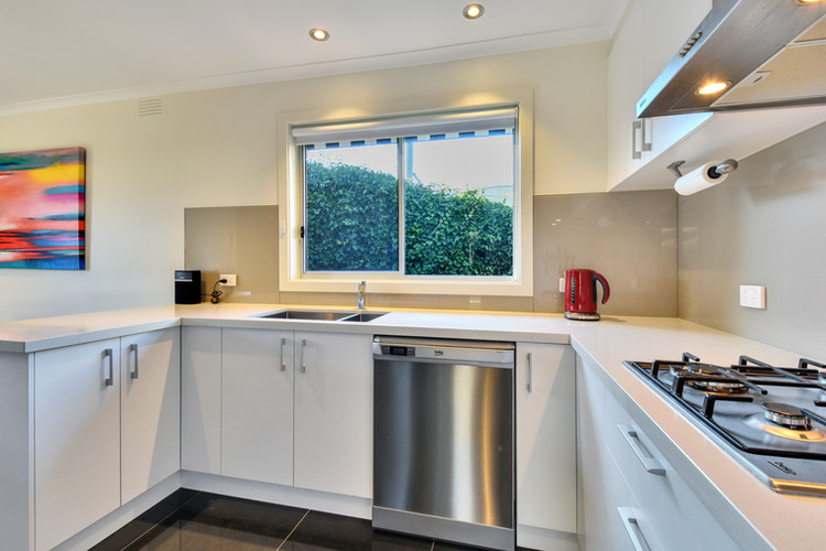 Modern kitchen with stone bench tops, gas cooking and dishwasher