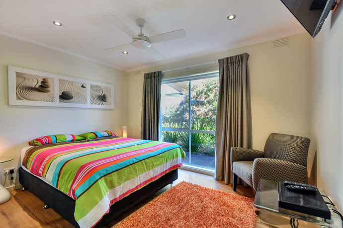 Bedroom 1 with queen size bed, ceiling fan and built in robes