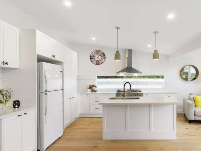 Modern kitchen with stone bench tops, dishwasher and gas cooking