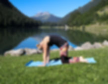 woman doingcat yoga pose in front of a lake