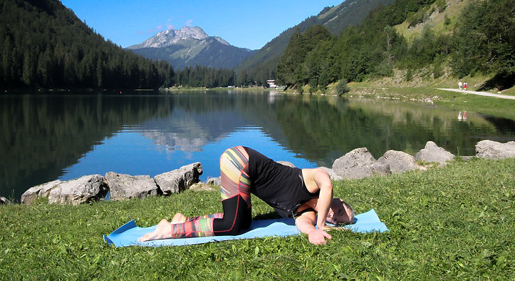 woman doing a yog pose on grass in front of a lake and mountains