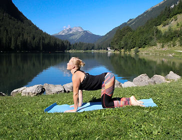 blonde woman doing cow pose yoga on grssin front of a lake