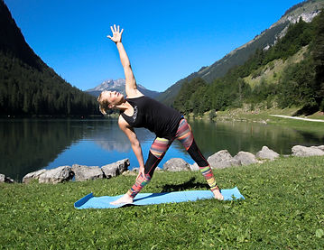 woman standing on a blue mat arms reaching, up and down with a lake and nature in the back ground