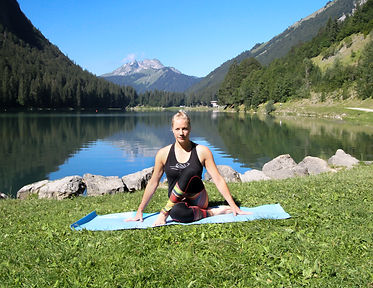 woman sitting on blue mat i front ofa lake with mountains in the back ground