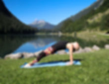 woman doing a back bend on a blue mat with a lake an mountain in the back ground