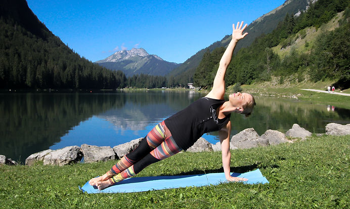 woman doing side plank yga pose in front of lake and mountain