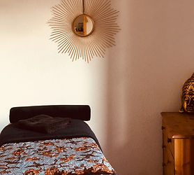 room massge couch with black towels and gold sun mirror