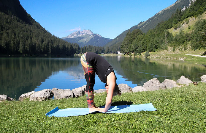woman stading on a blue mat folding forward from the waist with a lake, nature andmountains in the back ground