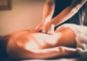 woman lying down having her back massaged