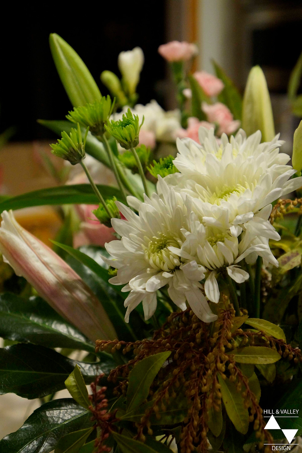 White chrysanthemums, pink and white roses, pink carnations, lilies