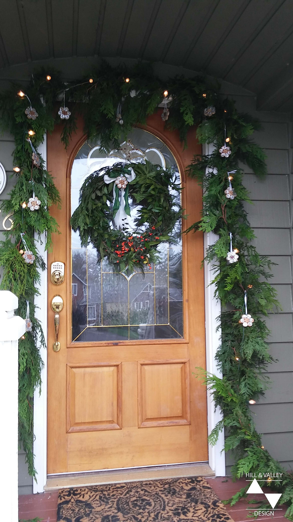 Porch/entry door decorated for Christmas with wreath, lights, ornaments, and garland.