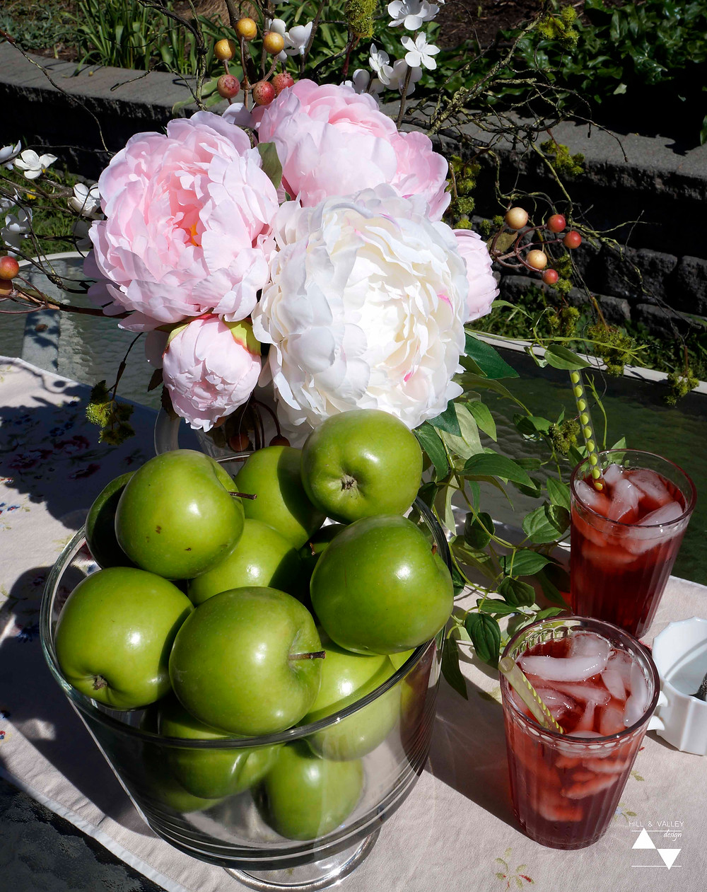 Flowers, apples, iced tea on table