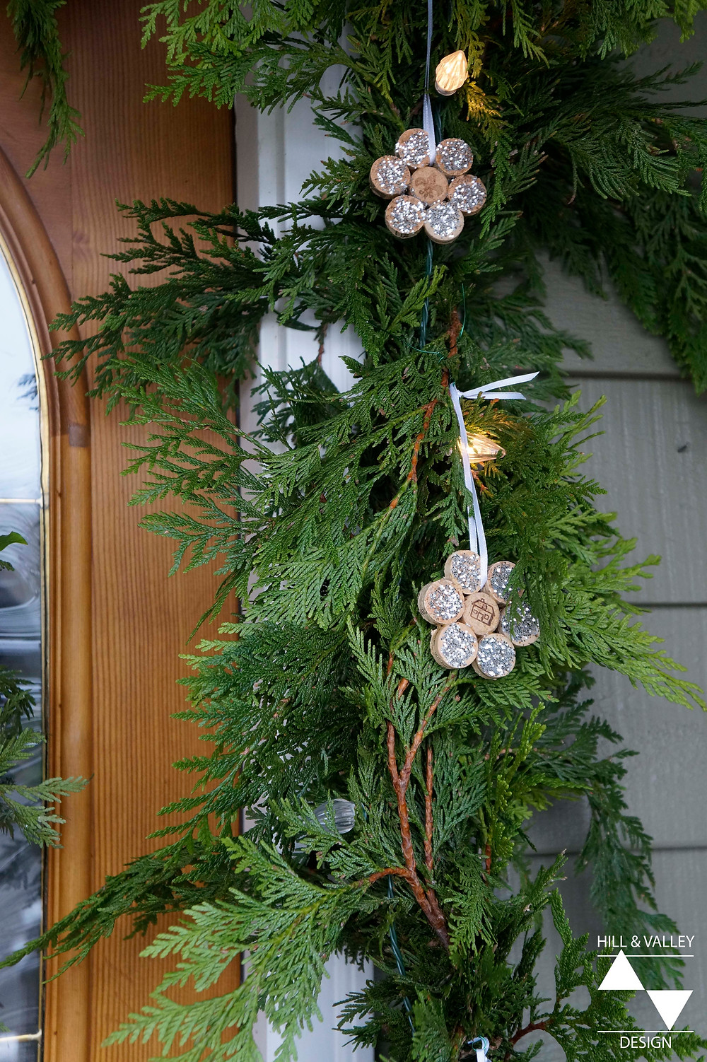Front door, cedar garland, white lights, glitter, ornaments
