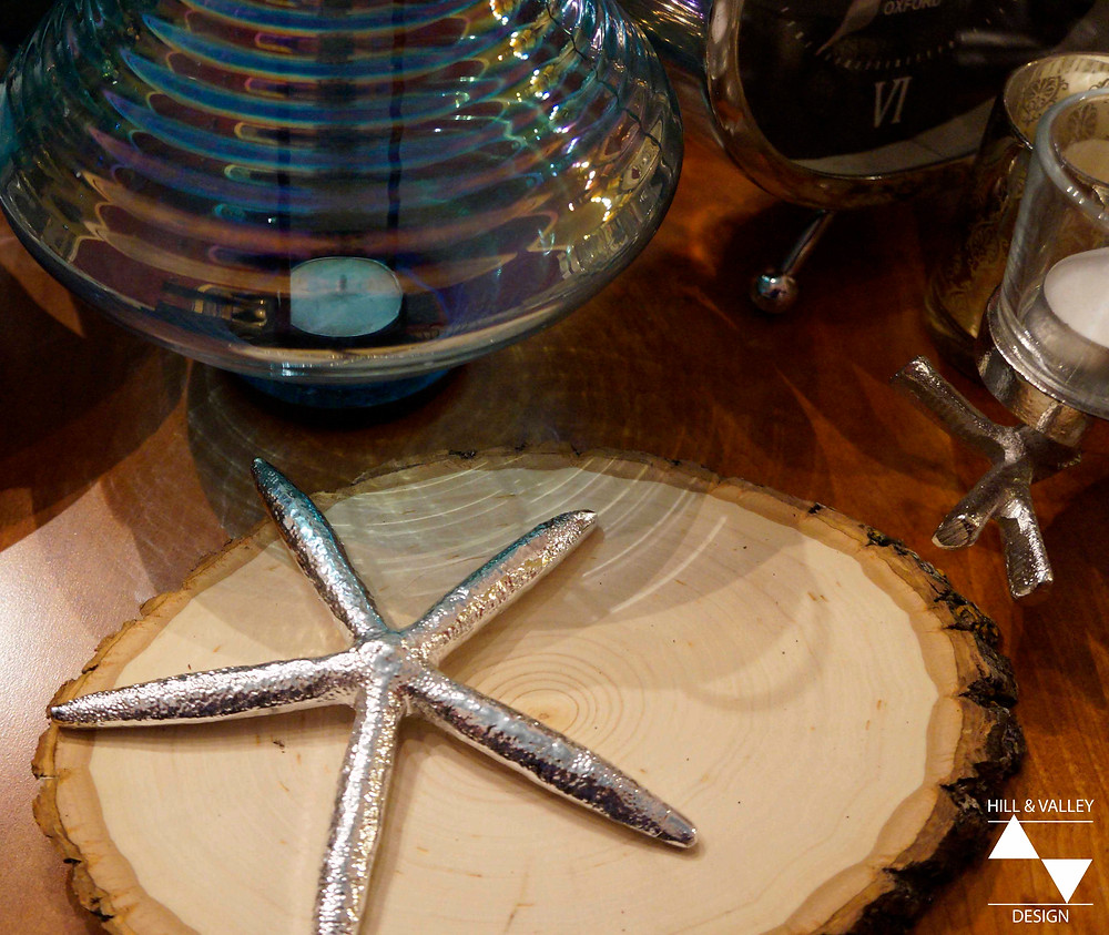 silver starfish and unfinished wood slice