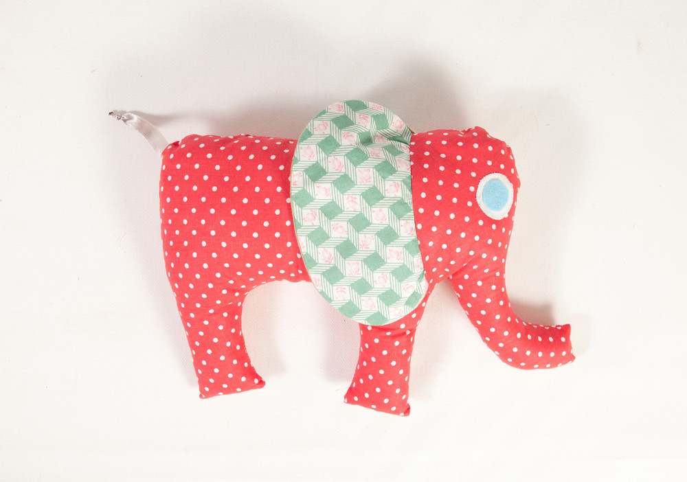 a red spotty quilted elephant, ribbon tail, green patterned fabric ears and blue eyes on a white background.