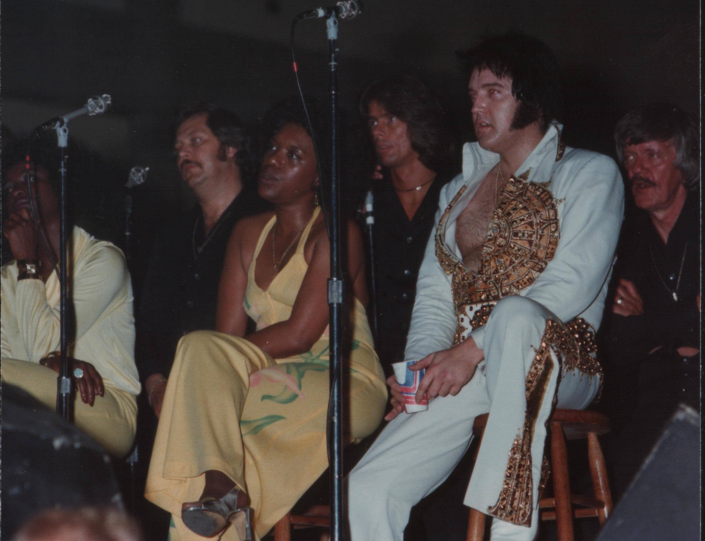 Elvis taking a rest while introducing the Band