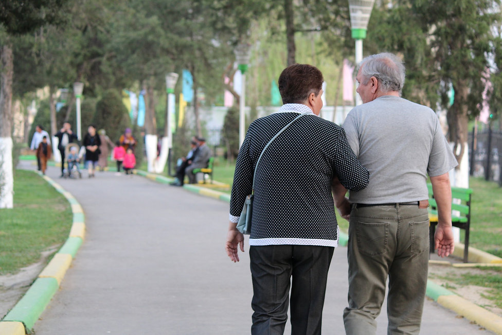 Photo of elderly man walking arm in arm with family member.