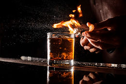 The bartender makes flame over a cocktai
