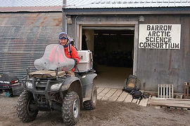 """A person rides a 4-wheeler out of a building with a sign that reads """"Barrow Arctic Science Consortium"""""""