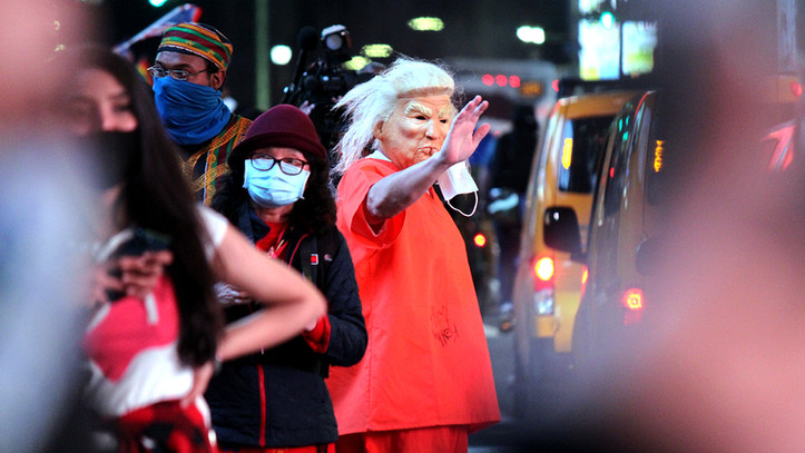 A man dressed in a Donald Trump mask walks through Times Square, Nov. 7, 2020, New York City.