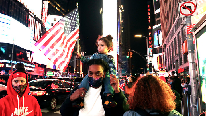 A girl joins celebrations  in Times Square after Joe Biden is declared winner of the US presidential elections, Nov. 7, 2020, New York City.