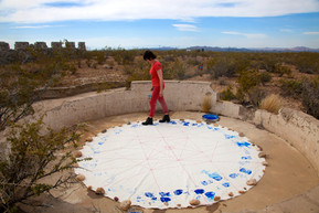 """Elizabeth Leister stitched the city plan designed by Alice Constance Austin into this circular piece of canvas. She then put on two boots, with the words """"History"""" and """"Memory"""" carved into the soles, and walked in circles along the perimeter of the canvas, splashing water from a bucket as she walked. The piece reflects the idea of repetition without progress, as well as the failure of the Llano project."""