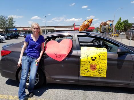 blonde teacher next to car