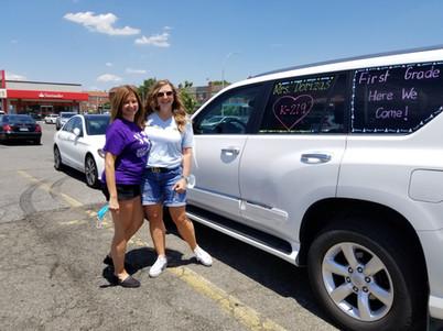 two ladies next to white car