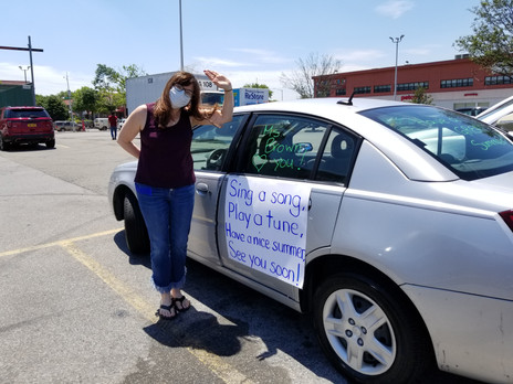 lady next to car with sign waving