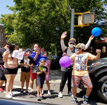family waving on street
