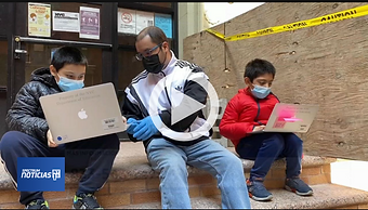 a man and two boys with laptops