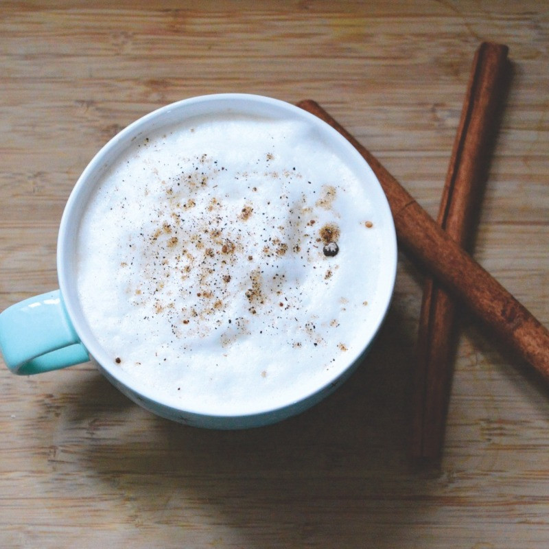 Steamed milk in morning coffee with a dash of cinnamon