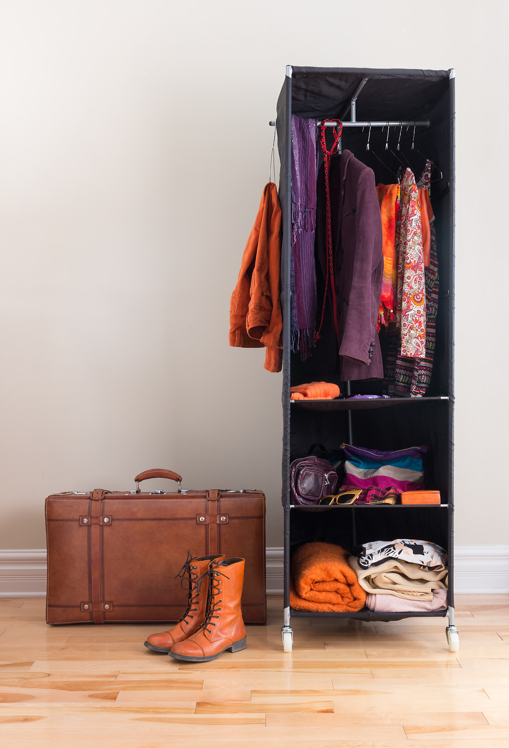 one brown colored leather suitcase, one pair of tan colored lace-up boots, and a portable black wardrobe with a small collection of clothes hanging and folded up within it.
