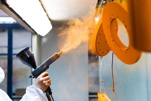 Powder coating of metal parts. A woman i