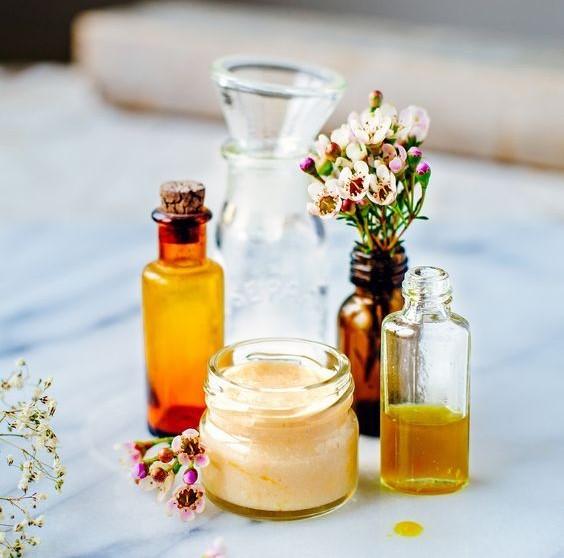 Hair oils in trendy glass bottles with Shea butter in a glass jar & few cute flowers in a glass bottle.