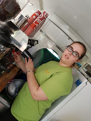 A girl wearing spectacles working with a coffee machine while lookng front
