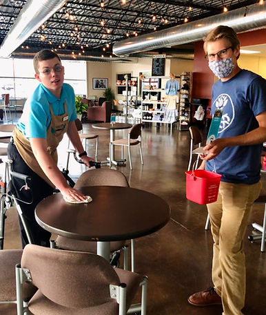 Riley wears a bright blue shirt and a tan apron as he wipes down a table. Sammy stands to his left holding a red bucket and wearing a blue shirt with tan khakis. Both boys are wearing glasses.