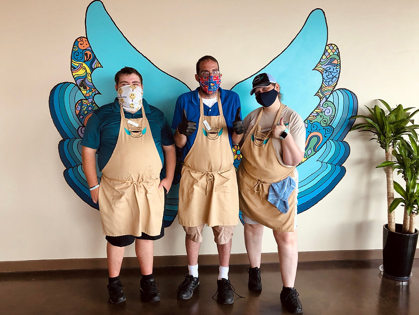 From left to right: Aaron, Kevin, and Dena pose together in front of a bright and colorful mural of angel wings. They are wearing tan aprons with the Love Coffee logo.