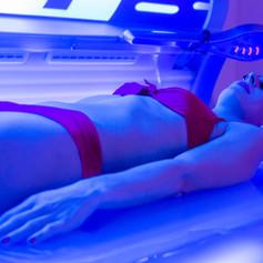 Woman in bikini tanning in wellness spa