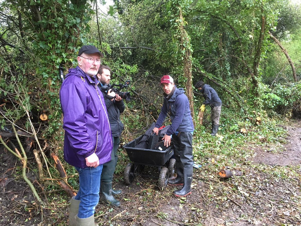 Group of volunteers around a wheelbarrow.