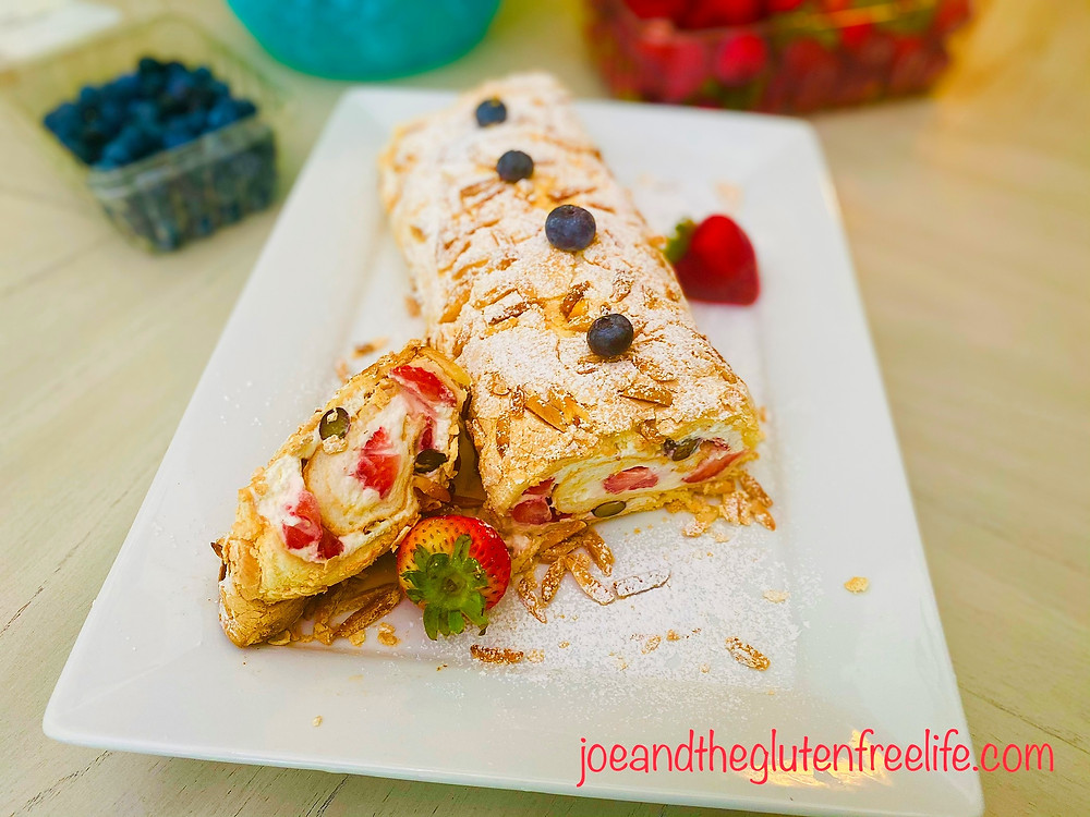 Beautiful meringue roll with fresh Strawberries and Blueberries, orange cream, and almonds!