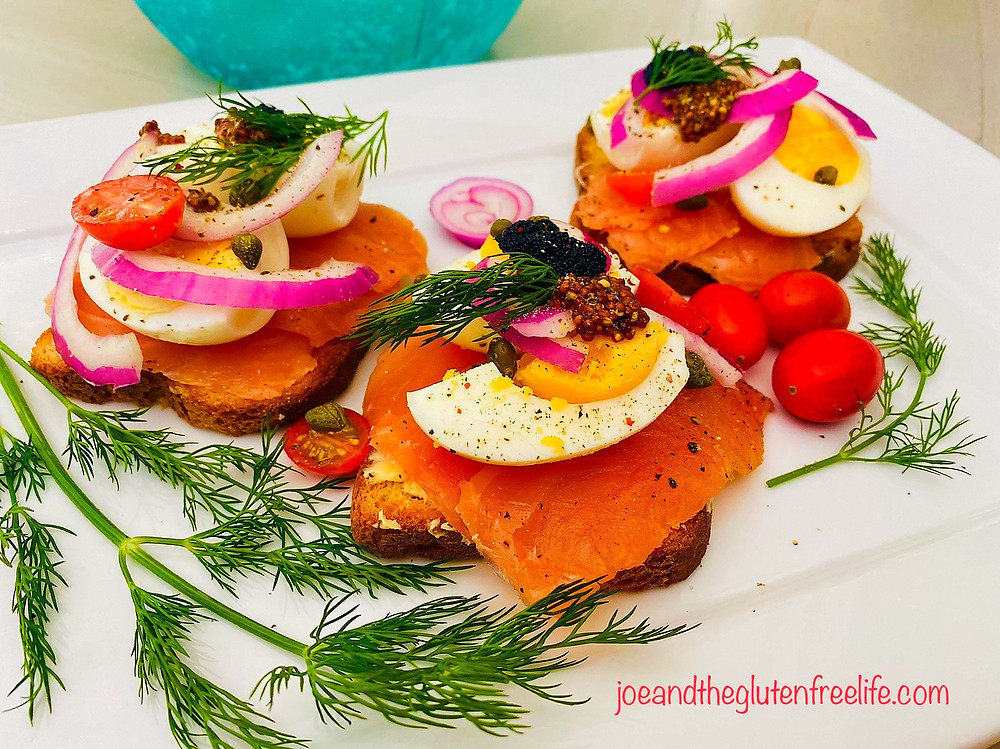 Open face salmon sandwich with boiled eggs, capers, onions, butter, and caviar.