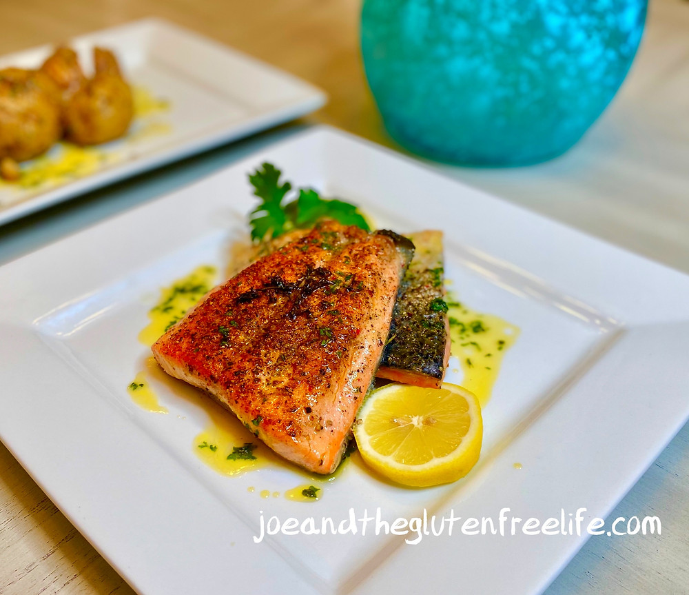 Delicious pan seared salmon with a pepper crust and cooked in a butter garlic and herbs sauce.