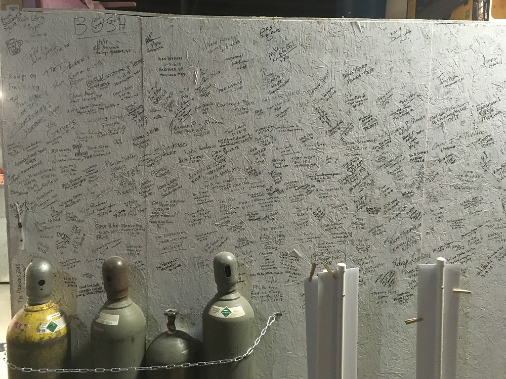 tour wall at inventors brewpub with signatures